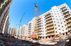 New tall apartment buildings under construction with cranes against blue sky  - stock photo