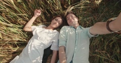 Young lovely couple lying in a field of wheat, having a good time and taking Stock Footage