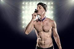 Composite image of swimmer kissing his gold medal against spotlight Stock Photos
