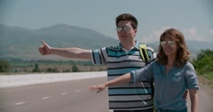 Young couple standing on an empty road, hitchhiking, mountainous terrain, slow Stock Footage