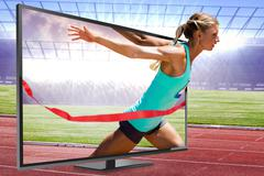 Sportswoman finishing her run against race track - stock photo