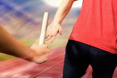 Athlete passing a baton to the partner against athletic track in a stadium Stock Photos