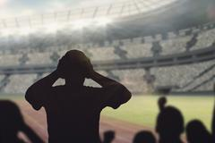 Silhouettes of football supporters against view of a stadium - stock illustration