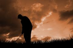 Golfplayer about to swing a golf ball against cloudy sky Piirros