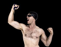 Swimmer posing with gold medal against black background - stock photo