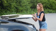 Young girl with a broken car with open hood Stock Footage