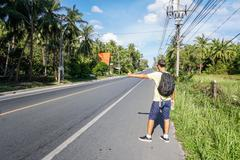 Male tourist hitchhiking on roadside by highway on Samui island, Thailand, Asia - stock photo