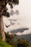 Man Swinging On A Swing In Banos De Agua Santa - stock photo