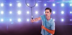 Badminton player playing badminton against composite image of blue spotlight - stock photo