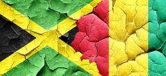 Jamaica flag with Guinea flag on a grunge cracked wall - stock illustration