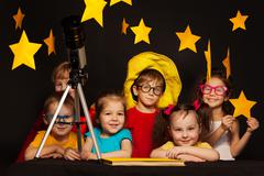 Children studying astronomy with telescope Stock Photos