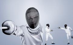 Man wearing fencing suit practicing with sword against grey vignette Kuvituskuvat