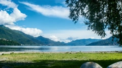 Lake Como with grass, moving clouds and tree Timelapse - stock footage