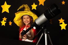 Happy girl in sky watcher costume with a telescope - stock photo