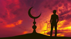 The man stand near the Islam symbol against the background of sunset. Real time  - stock footage