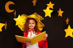 Little sky watcher studying stars with big book - stock photo