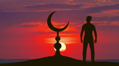 The man stand near the Islam symbol against the background of sunset. Time lapse Stock Footage