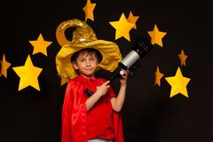 Boy in sky watcher costume with telescope - stock photo
