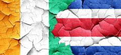 Ivory coast flag with Costa Rica flag on a grunge cracked wall Stock Illustration