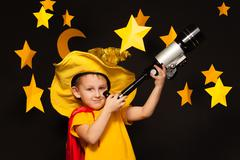 Little sky watcher looking through a telescope - stock photo