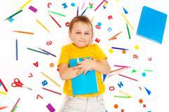 Kid boy holding textbook laying among stationery - stock photo