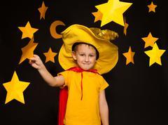 Little boy in stargazer costume among paper stars - stock photo