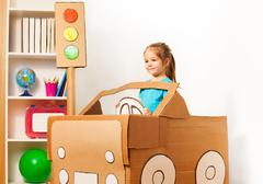 Cute little girl driving her toy cardboard car - stock photo