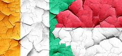 Ivory coast flag with Indonesia flag on a grunge cracked wall - stock illustration