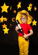 Young stargazer with telescope against starry sky - stock photo