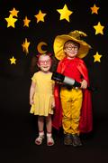Kids in sky watchers costumes with a telescope Stock Photos