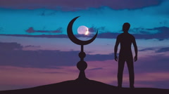 The man stand near the Islam symbol against the background of sunset. Time lapse - stock footage