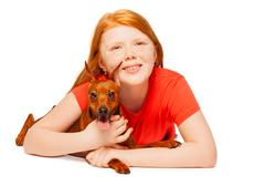 Nice young girl with her dog lay down portrait Stock Photos