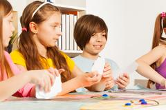 Four kids playing cards for a pastime - stock photo