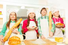 Four young cooks with bakery food at the kitchen - stock photo