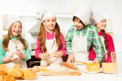 Four happy young cooks making dough bakery - stock photo