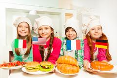 Four kids representing meal of different countries - stock photo