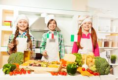 Young cooks preparing traditional Italian meal - stock photo