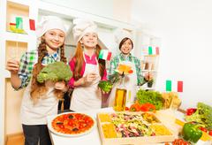 Three young Italian cooks at the kitchen - stock photo