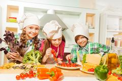 Three young cooks cutting pizza at the kitchen - stock photo