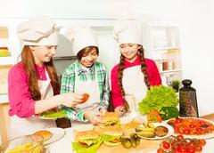 Three young cooks preparing hamburgers at kitchen - stock photo