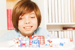 Smiling boy playing ice hockey table board game - stock photo