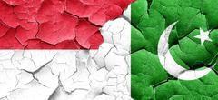 Indonesia flag with Pakistan flag on a grunge cracked wall - stock illustration