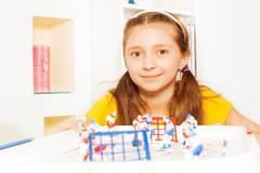 Beautiful girl playing ice hockey table board game - stock photo