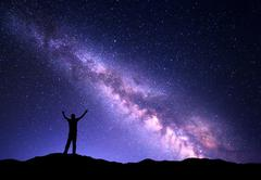 Night colorful landscape with purple Milky Way and silhouette of a man - stock photo