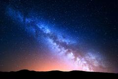 Night landscape with colorful Milky Way and yellow light at mountains Stock Photos