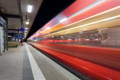 Modern railway station with high speed passenger train on railroad track in m Stock Photos