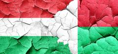 Hungary flag with Madagascar flag on a grunge cracked wall Stock Illustration
