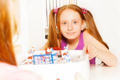 Cute girl playing ice hockey table board game - stock photo