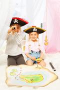 Two cute pirates looking through a toy spyglass - stock photo