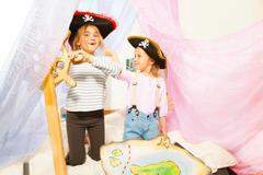 Funny girls in pirate's costumes steering the ship Stock Photos
